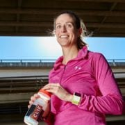 Woman in under armor pink half zip and clif water bottle