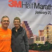 Happy couple standing in front of 3M Half Marathon poster