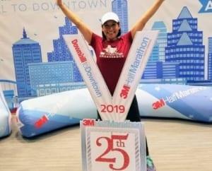Sara Ferniza, 2020 3M Half Ambassador, poses with giant 2019 3M Half Marathon medal.