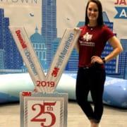 Brittany Bussey, 2020 3M Half Ambassador, poses with giant 2019 3M Half Marathon medal.