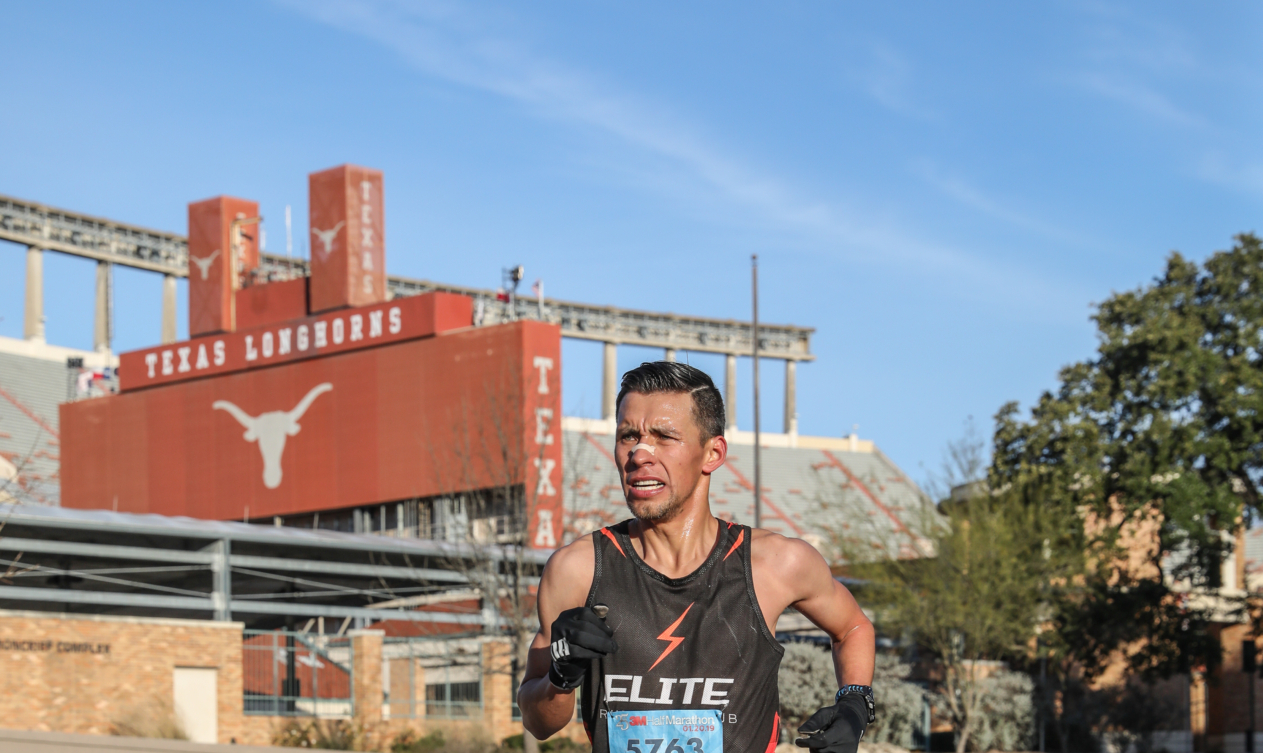 Runner passes through UT campus during the 2019 3M Half Marathon. Get to know Austin when you visit the places in our blog, like The University of Texas.