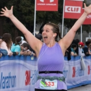 Runner crosses the 2019 3M Half Marathon finish line wearing her SPIbelt. SPIbelt is the Official Race Belt of the 2020 3M Half Marathon presented by Under Armour.