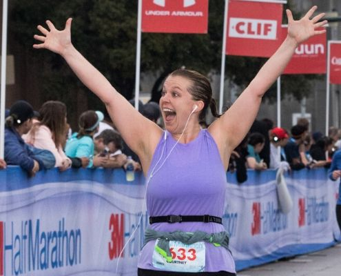 Runner crosses the 2019 3M Half Marathon finish line wearing her SPIbelt. SPIbelt is the Official Race Belt of the 2020 3M Half Marathon presented by Under Armour.