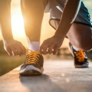 Image of runner tying their shoes as the sun rises. Use our blog's holiday training tips to stay on track for 3M Half Marathon.