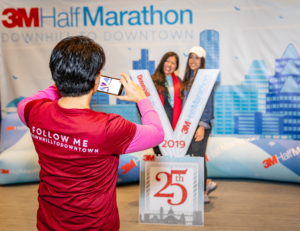 Image of a 3M Half Marathon Ambassador taking a photo of two runners at the 2019 3M Half Marathon expo. This blog has everything you need to get ready for the 2020 3M Half Marathon!