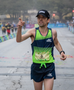 Image of David Fuentes crossing the 2018 Austin Marathon finish line in 4th place. He is running in the 26th annual 3M Half Marathon's elite field.