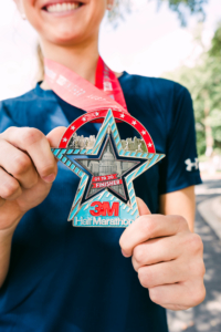 Image of runner showcasing the 2020 3M Half Marathon finisher medal. This blog has everything you need to get ready for the 2020 3M Half Marathon!