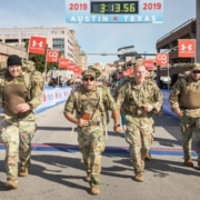 Image of four soldiers crossing the 2019 3M Half Marathon finish line in full gear. Meet our friends will make 2020 3M Half Marathon unforgettable and remember running is better with friends.