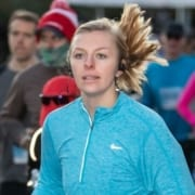 Picture of a young woman running the 2019 3M Half Marathon while listening to head phones. She'll add songs to her running playlist from this list of March running playlist additions!