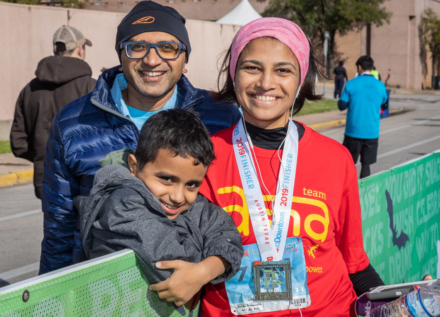 Image of a mom posing with her son and husband at the 2019 3M Half Marathon finish line. Nominate your mom in this blog post for the Mother's Day giveaway!