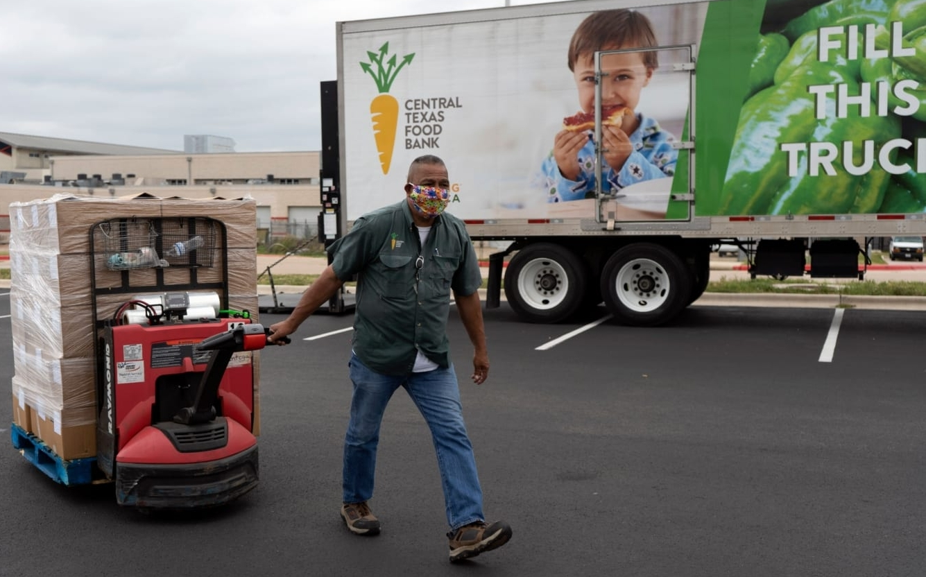 An employee of the Central Texas Food Bank, the 2021 beneficiary of the 3M Half Marathon, pulls a pallet jack full of food after unloading a truck.