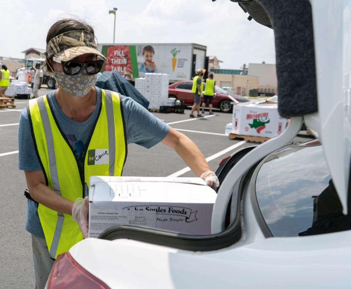 An employee of the Central Texas Food Bank, the 2021 beneficiary of the 3M Half Marathon, loads a box into the trunk of a car.