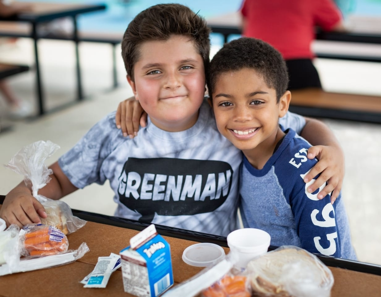 Two children enjoy a meal from the Central Texas Food Bank, the 2021 beneficiary of the 3M Half Marathon.