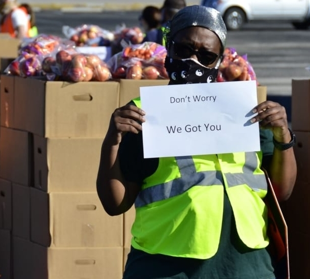 """Image of Central Texas Food Bank worker in a mask and hi-vis vest holding a sign saying, """"Don't worry, we got you."""" The Central Texas Food Bank is the beneficiary of the 2021 3M Half Marathon."""