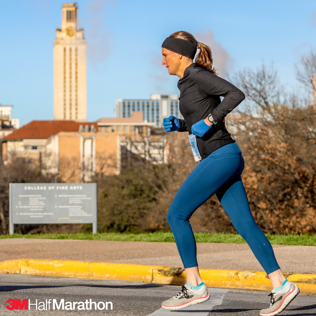 Female runner during the 2019 3M Half Marathon. She's running towards the finish line in running shoes specifically for running. Use our tips to ensure you pick the right running shoes for you at https://downhilltodowntown.com/right-running-shoes-for-you/