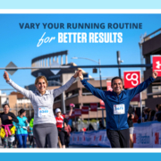 Two runners cross the 2020 3M Half Marathon finish line with their arms raised in the air and big smiles on their faces. Text on design reads Vary Your Running Routine for Better Results. Read more at https://downhilltodowntown.com/vary-your-running-routine/