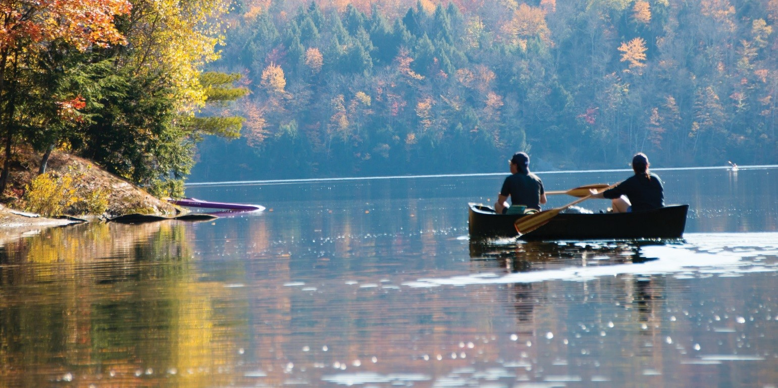 A man and woman paddle a canoe on a calm lake edged by colorful trees in fall.