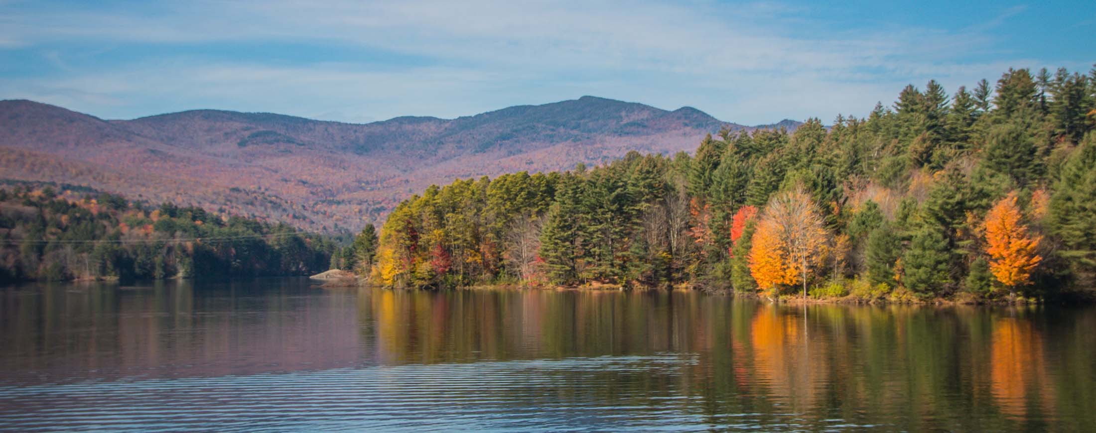 A view of a lake surrounded by mountains and trees that are turning red, orange and yellow in the fall. ge an