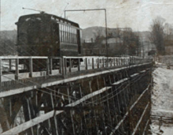A black and white picture of an 1800s trolley on an elevated wooden track.