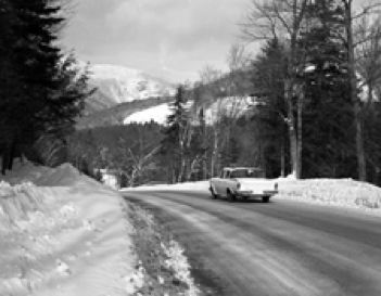 A black-and-white photo of a 1950s-style car driving through the mountains in winter.