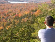A man who is hiking takes in the view from a mountain top of fall foliage with a lake in the distance.
