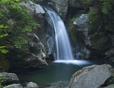 A waterfall surrounded by boulders plunges from atop a small cliff in a forest.