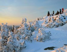 A group of hikers stand at the top of a mountain covered in snow watching the sunset.