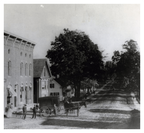 A black and white photo of a village street with horses and buggies.