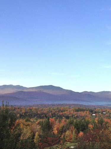 A sweeping view of mountains in fall with forests and leaves of vibrant colors.