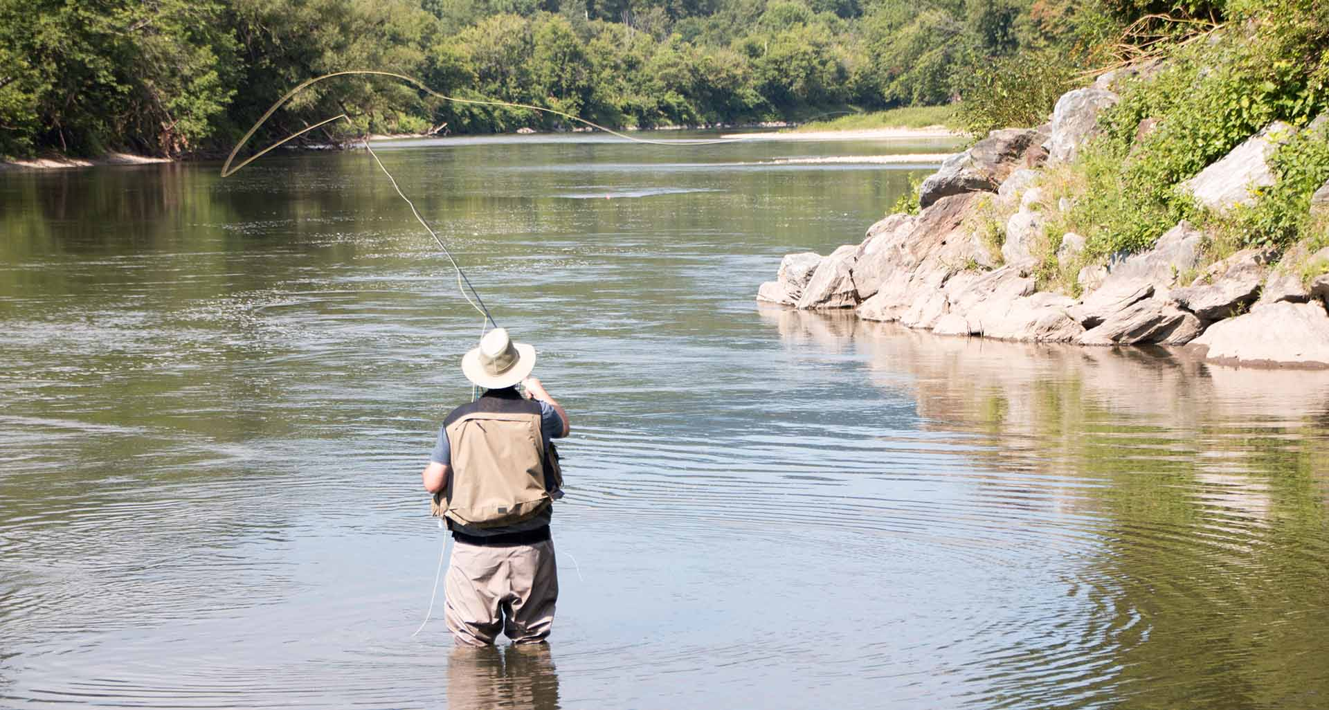 A man stands in a river wearing waders and casting a fishing pole.