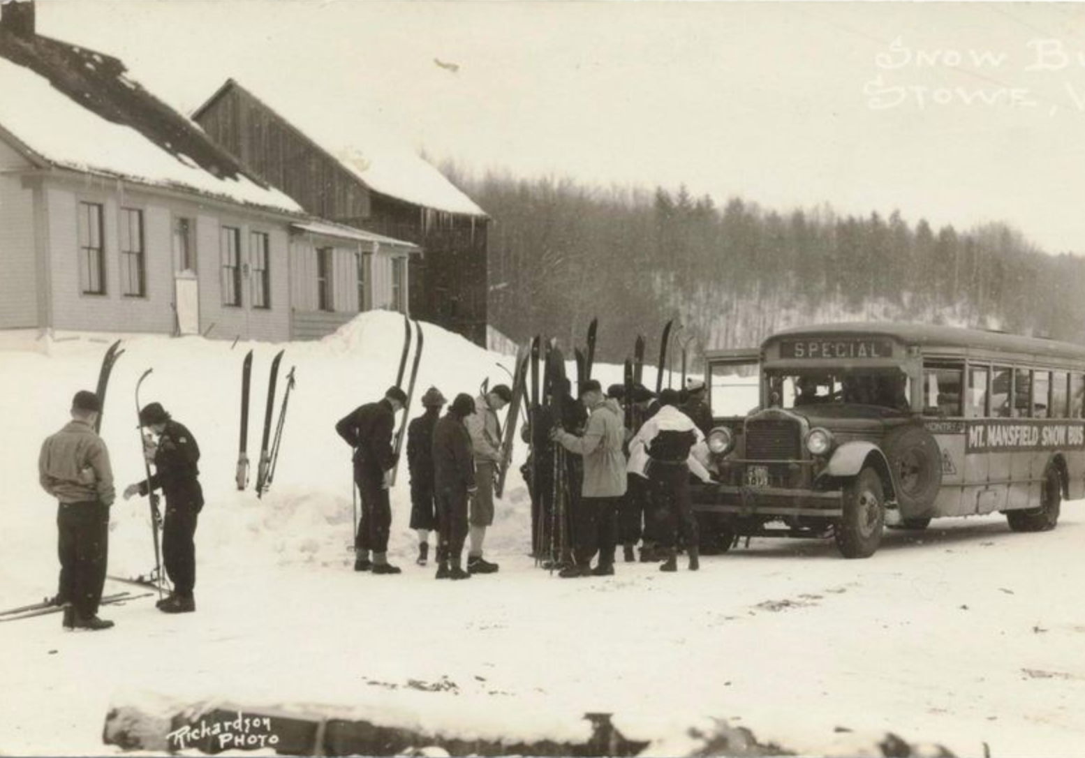 A black-and-white photo of people getting off a bus with skis.