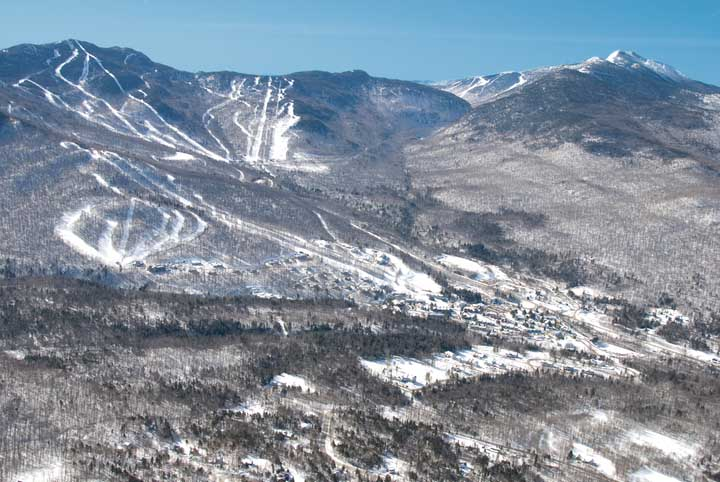 A distant aerial view of the skil trails on the three mountains of Smugglers' Notch Resort in winter.