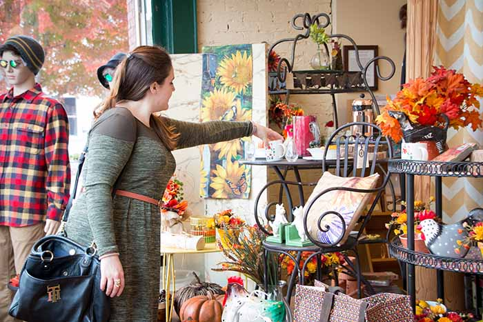 A young woman shops in a boutique stocked with gifts and unique items.