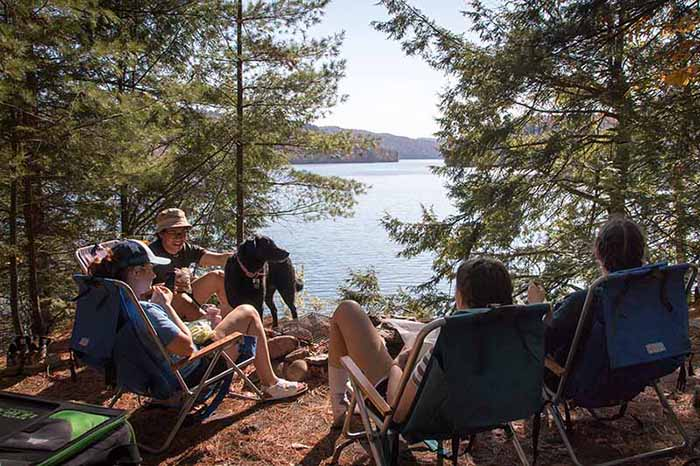 Two couples and a dog gather lakeside at a tent site on a large lake.