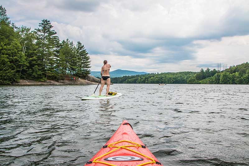 A woman paddleboards while the photographer takes a picture from their kayak behind her.