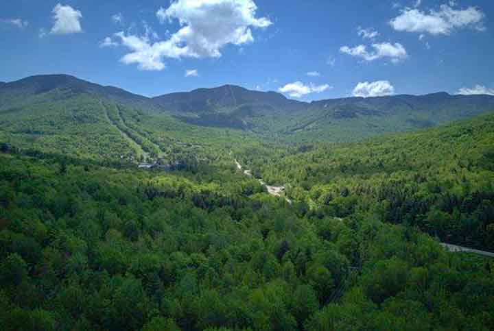 An aerial view of rolling green mountains in summer.