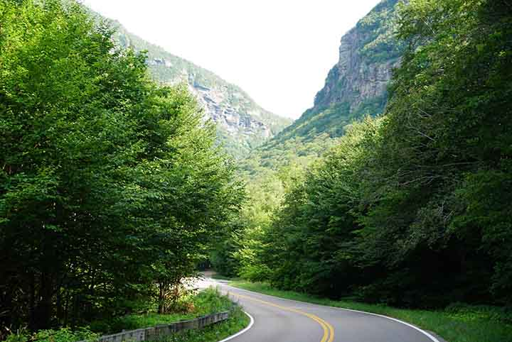 A paved road leads into the forest and toward the hills of Smugglers' Notch.