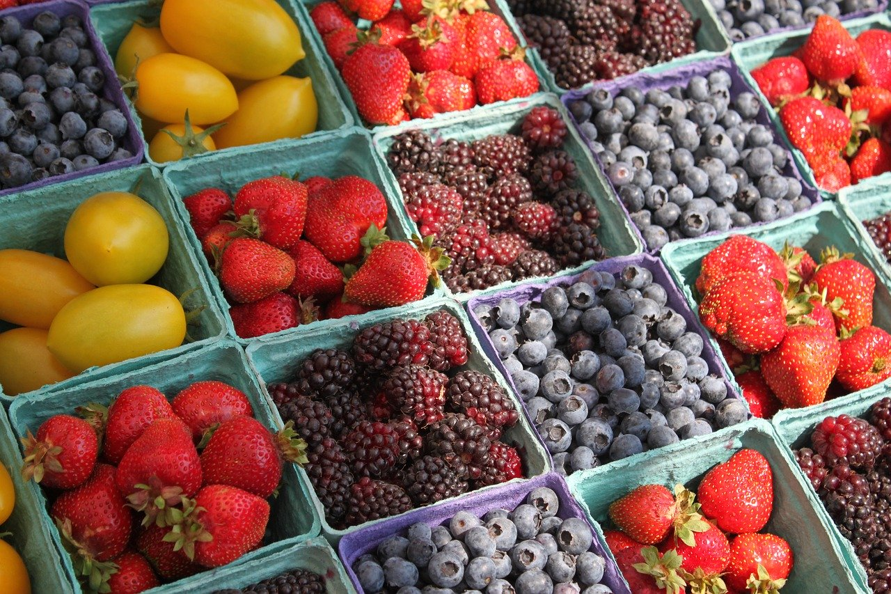 Baskets of strawberries, blackberries, blueberries, and yellow tomatoes make a colorful outdoor display.