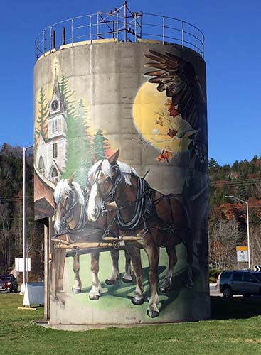 A painting of a team of horses with a church and a sun on a 36-foot silo.