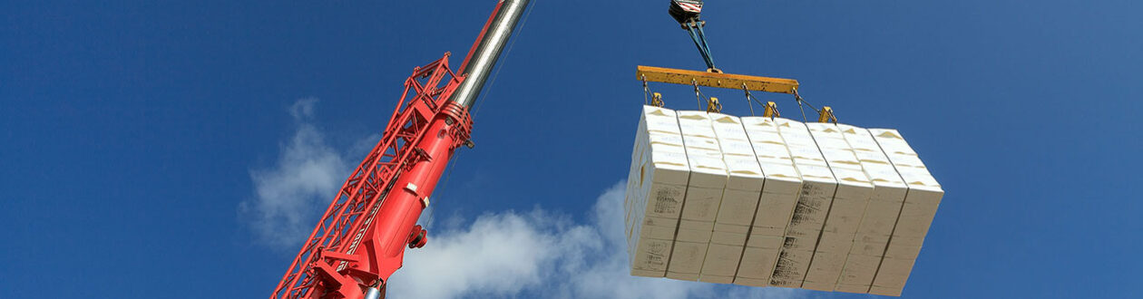 Crane lowering pulp bales into a barge at the Mercer Stendal pulp mill in Arneburg, Germany