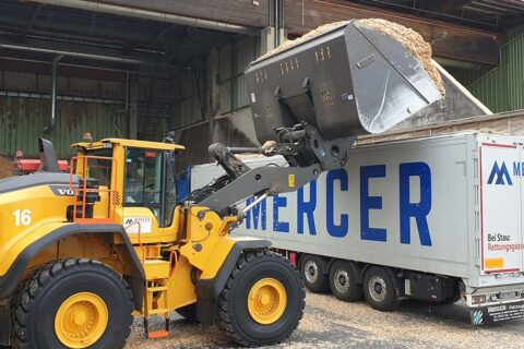 Front loader dumping chips in a Mercer Holz Chip truck, parked at the Mercer Timber Products sawmill in Friesau, Germany