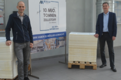 André Listemann, Managing Director Mercer Stendal, stands with team member and pulp sheet stacks to commemorate 10 million tonnes of production