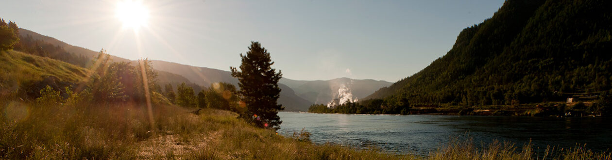 Celgar pulp mill seen in the distance along the Nelson River, British Columbia, Canada, at sunrise