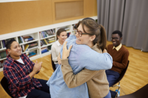 Two people hug at an Autism group therapy session.