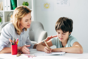 A Certified Language Therapist guided a young boy through his dyslexia treatment reading skills.
