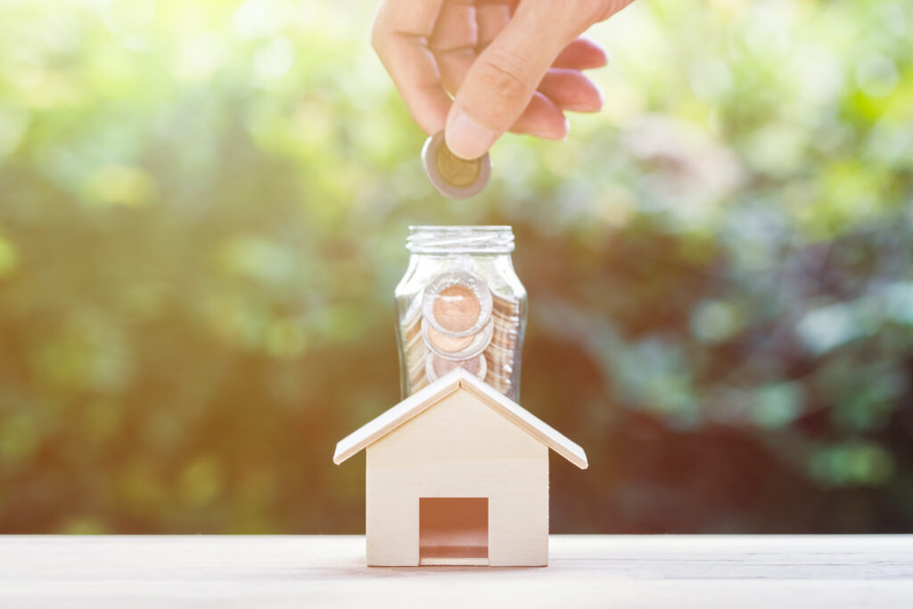 Saving money, home loan, mortgage, a property investment for future concept : A man hand putting coins over small residence house and glass jar with green nature background. A sustainable investment.
