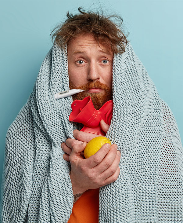 man covered in blanket, sick with thermometer in mouth