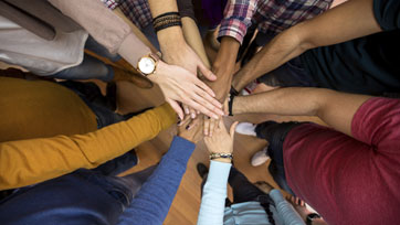 Group of people with their hands in the middle