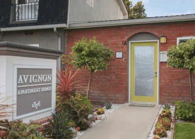 Entrance to Avignon Apartment Homes with landscaping and sign