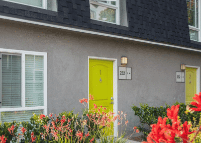 closed yellow front door to apartment home and flowers
